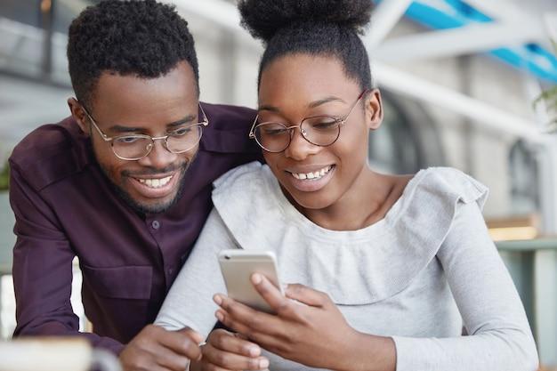 Lindo casal africano navega na internet em um telefone inteligente, reserva bilhetes online enquanto vai passar as férias de verão em um país tropical, tem expressões felizes.