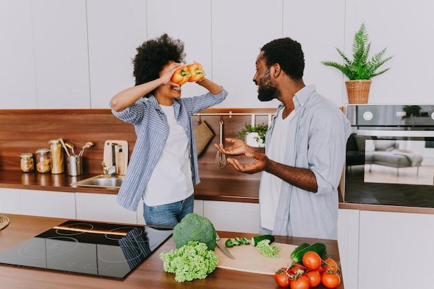 Lindo casal afro-americano cozinhando em casa