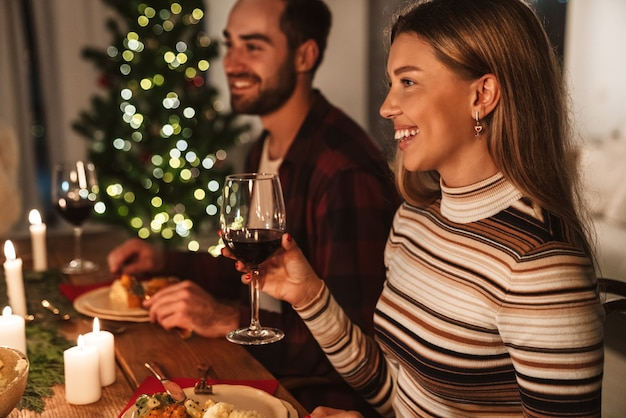 Lindo casal alegre bebendo vinho e rindo enquanto janta de natal em um quarto aconchegante