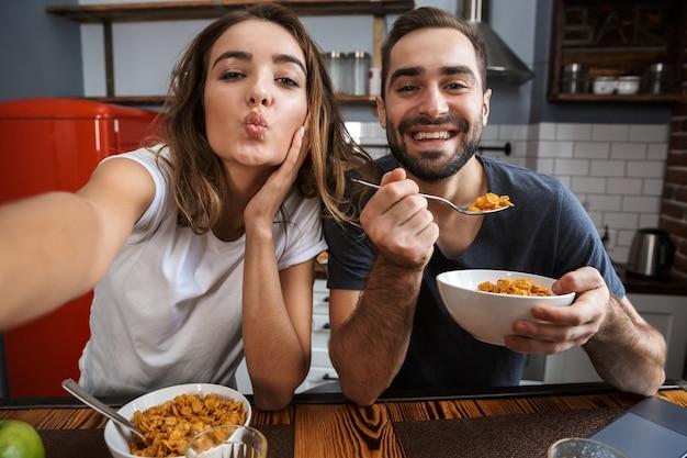 Lindo casal alegre tomando café da manhã na cozinha, tirando uma selfie