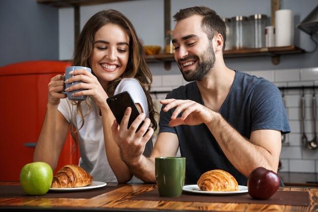 Lindo casal alegre tomando café da manhã na cozinha, usando telefone celular