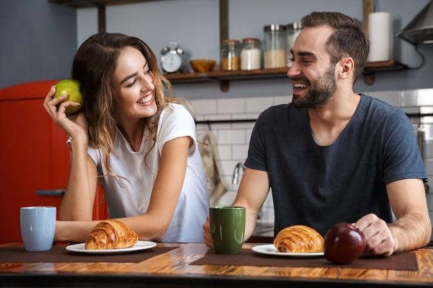 Lindo casal alegre tomando café da manhã na cozinha