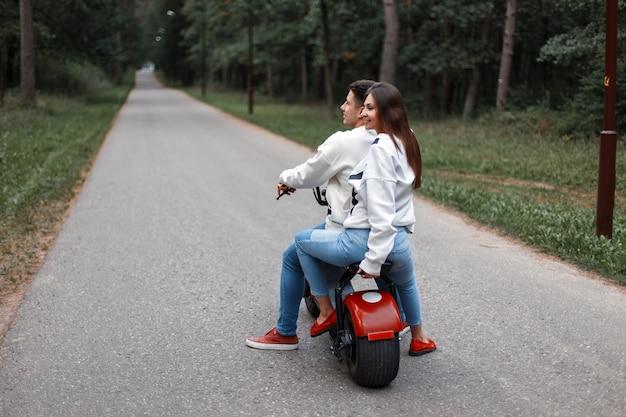 Lindo casal andando de bicicleta elétrica em uma floresta na estrada