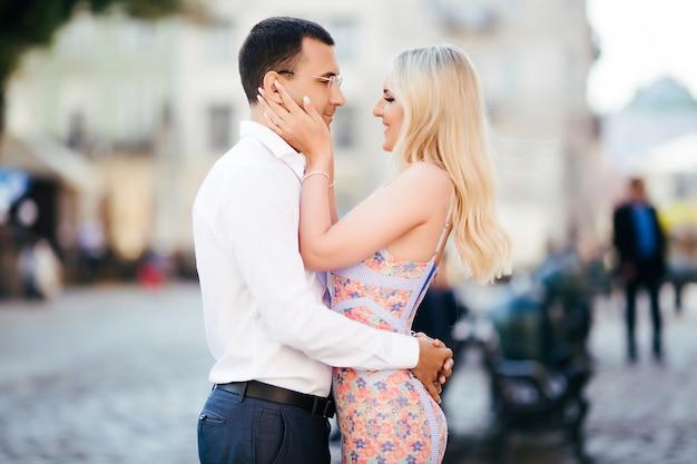 Lindo casal andando pelo quarteirão. homem de cabelos escuros em uma camisa branca, abraçando uma loira em um lindo vestido