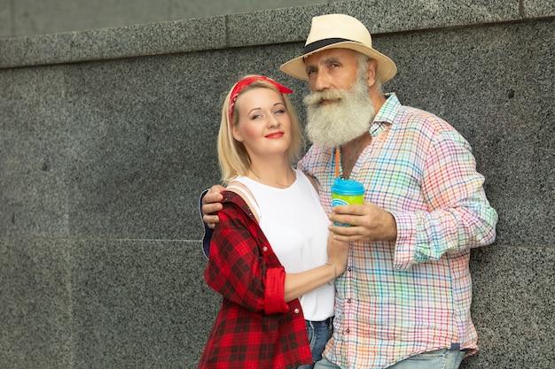 Lindo casal ao ar livre. homem barbudo maduro e mulher jovem.
