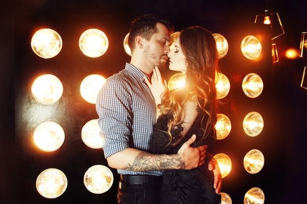 Lindo casal apaixonado, abraçando-se no contexto de luzes brilhantes
