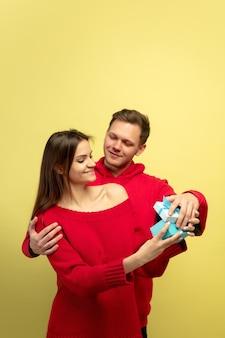 Lindo casal apaixonado abrindo presente na parede amarela do estúdio