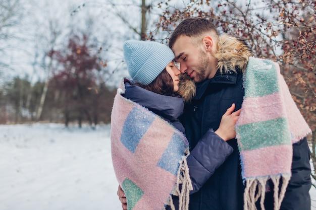 Lindo casal apaixonado andando e abraçando na floresta de inverno. pessoas aquecimento coberto com manta