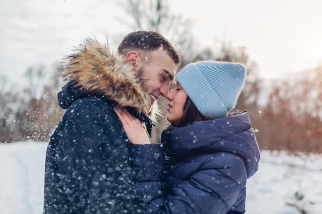 Lindo casal apaixonado andando e abraçando na floresta de inverno. pessoas se divertindo ao ar livre