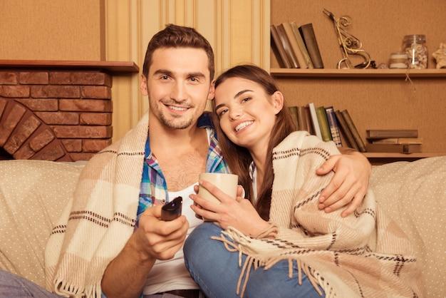 Lindo casal apaixonado assistindo tv sentado em um xadrez segurando uma xícara
