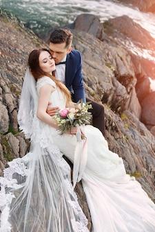 Lindo casal apaixonado beijando enquanto está sentado nas rochas perto do rio. casal de noivos ao pôr do sol e rios, amor e sentimentos ternos.