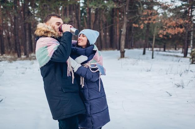 Lindo casal apaixonado caminhando juntos na floresta de inverno. pessoas bebendo chá quente na garrafa térmica