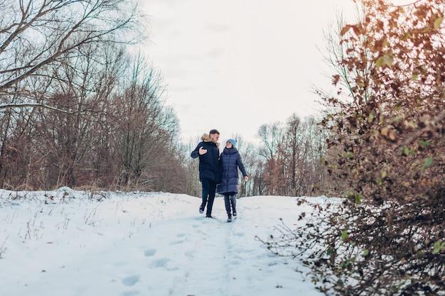 Lindo casal apaixonado caminhando juntos na floresta de inverno. pessoas se divertindo ao ar livre