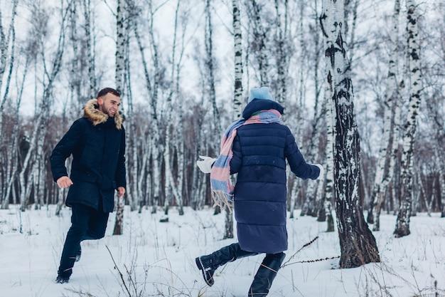 Lindo casal apaixonado correndo juntos na floresta de inverno. pessoas se divertindo ao ar livre
