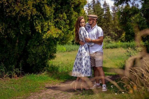 Lindo casal apaixonado de mãos dadas e olhando um para o outro no jardim verde