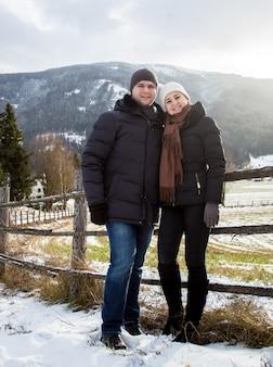 Lindo casal apaixonado e sorridente posando contra os alpes austríacos cobertos de neve