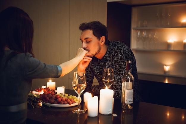 Lindo casal apaixonado em um jantar romântico à luz de velas em casa, homem beijando a mão