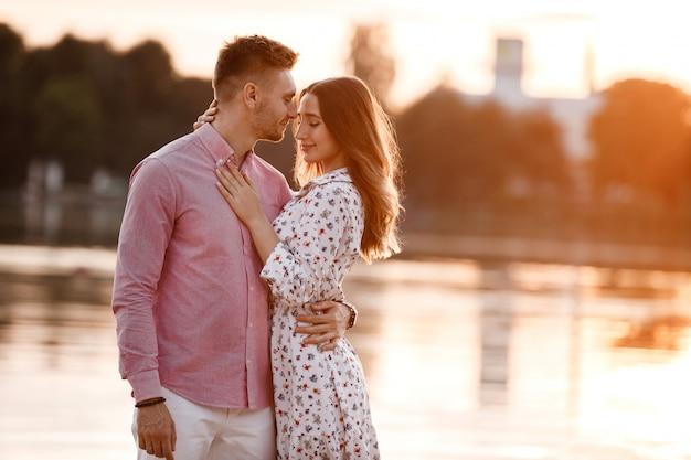 Lindo casal apaixonado está de pé e abraçando perto do lago na sunset. lindo casal feliz se divertindo perto do ar livre. conceito de feliz feriado