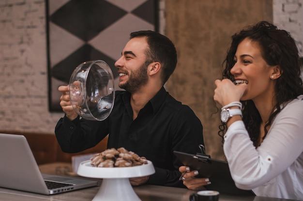 Lindo casal apaixonado flertando em um café, trabalhando juntos. amor e negócios. conceito de estilo de vida