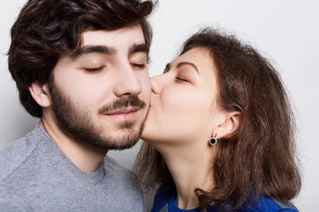 Lindo casal apaixonado isolado sobre parede branca. uma namorada beijando apaixonadamente seu namorado estiloso no queixo