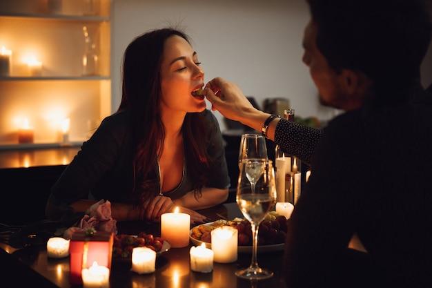 Lindo casal apaixonado jantando à luz de velas em casa, alimentando-se um ao outro