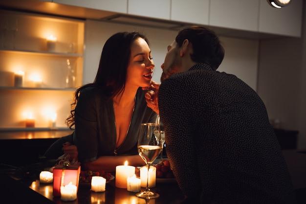 Lindo casal apaixonado jantando à luz de velas em casa, bebendo vinho, brindando, beijando