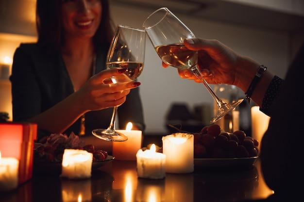 Lindo casal apaixonado jantando à luz de velas em casa, bebendo vinho, brindando