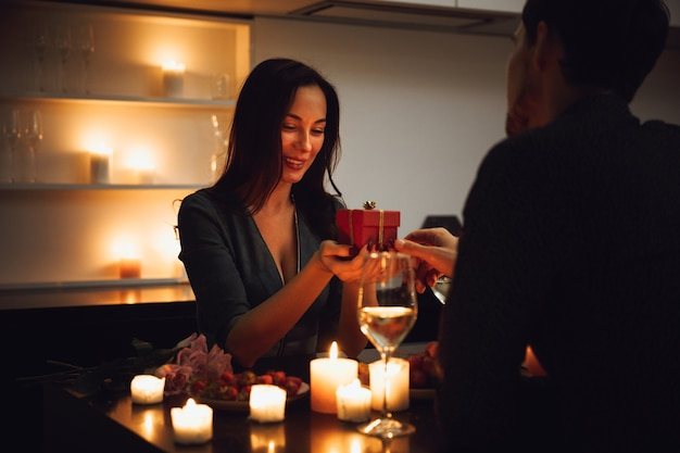 Lindo casal apaixonado jantando à luz de velas em casa, bebendo vinho, mulher recebendo uma caixa de presente