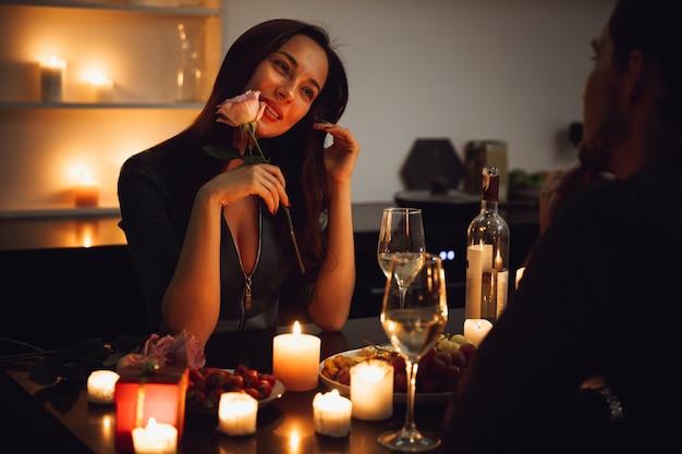 Lindo casal apaixonado jantando à luz de velas em casa, mulher cheirando uma flor