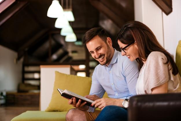Lindo casal apaixonado, lendo um livro no sofá
