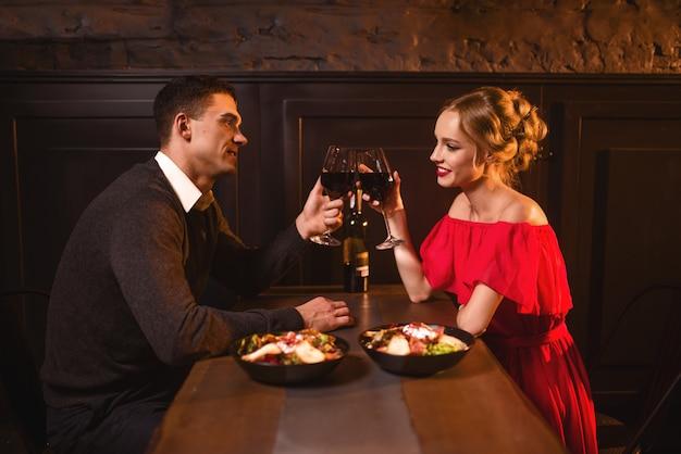 Lindo casal apaixonado levantou taças com vinho tinto no restaurante, encontro romântico. mulher elegante em vestido vermelho e seu marido, comemoração de aniversário