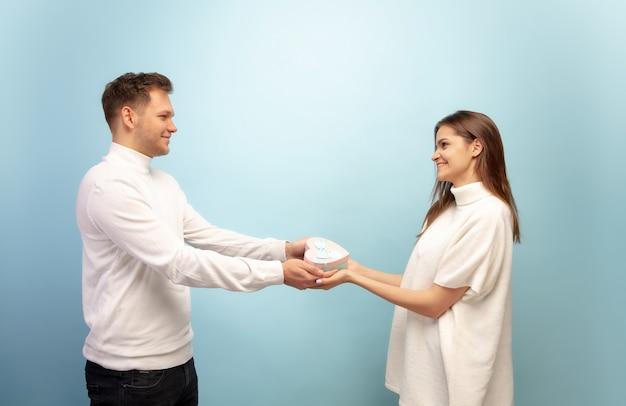 Lindo casal apaixonado na parede azul do estúdio