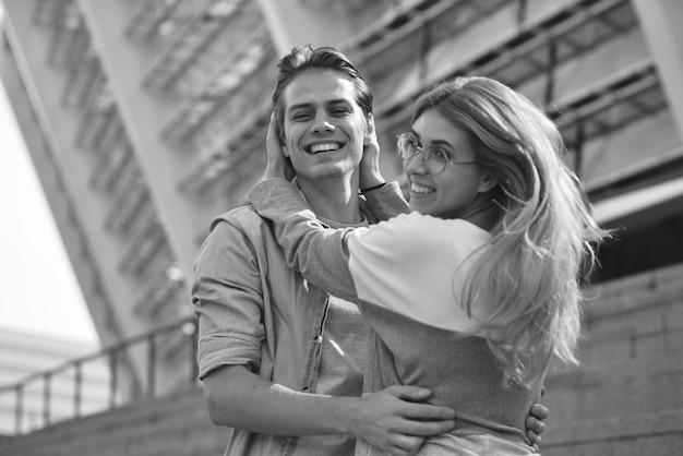 Lindo casal apaixonado, namorando ao ar livre e sorrindo.