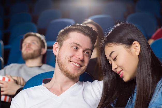 Lindo casal apaixonado no cinema homem feliz olhando sua namorada sorridente com amor
