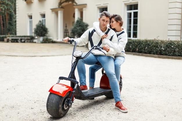 Lindo casal apaixonado por roupas elegantes em uma bicicleta de elétrons perto do hotel