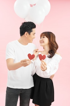 Lindo casal apaixonado por um balão vermelho segurando um formato de coração para o dia dos namorados