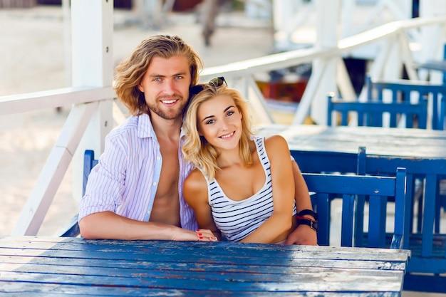 Lindo casal apaixonado se abraçando e sorrindo, sentado à mesa em um café aconchegante na praia
