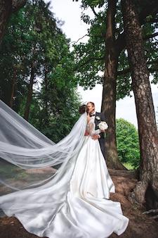 Lindo casal apaixonado se beijando no dia do casamento, eles estão de pé no parque