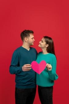 Lindo casal apaixonado segurando um coração rosa na parede vermelha do estúdio