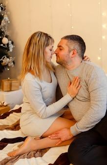 Lindo casal apaixonado, sentado ao lado de uma árvore de natal e desfrutando de momentos românticos. lindo casal se abraçando perto da árvore de natal. jovem casal passando o natal juntos