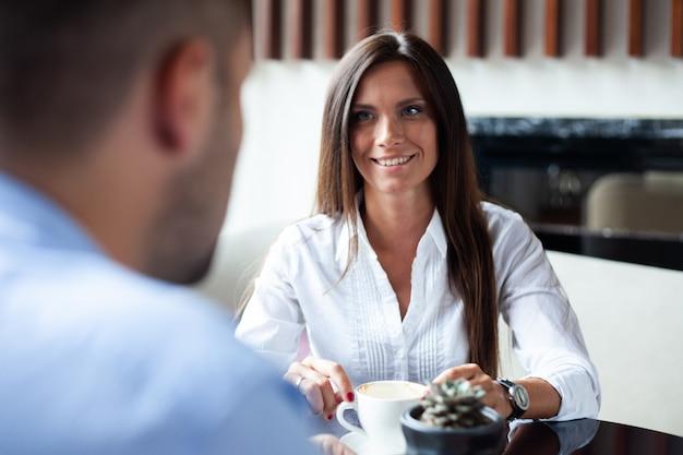 Lindo casal apaixonado, sentado em um café, desfrutando de um café e uma conversa