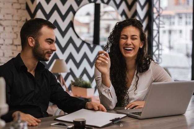 Lindo casal apaixonado, sorrindo em um café, trabalhando juntos. amor e negócios. conceito de estilo de vida
