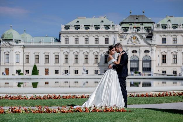 Lindo casal apaixonado, vestido com os trajes de casamento na frente do palácio no belo dia de sol, viagem de casamento