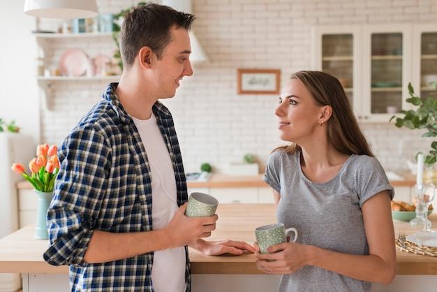 Lindo casal, apoiando-se na mesa e saboreando chá