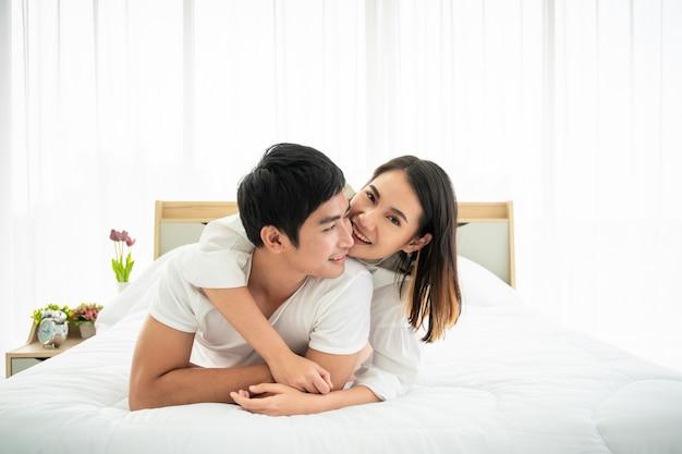 Lindo casal asiático deitado e conversando na cama. relação de casal.