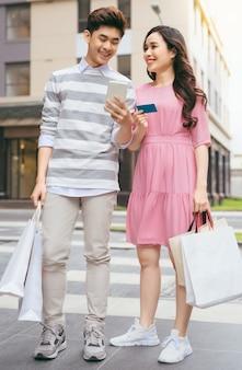 Lindo casal asiático fazendo compras com cartão de crédito na cidade