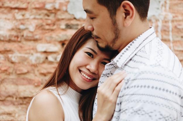 Lindo casal asiático por uma parede de tijolos
