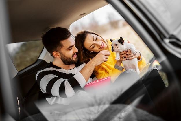 Lindo casal atraente feliz brincando com seu pequeno cachorro fofo em um carro.