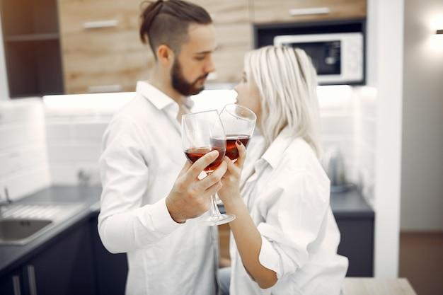Lindo casal bebe vinho tinto na cozinha