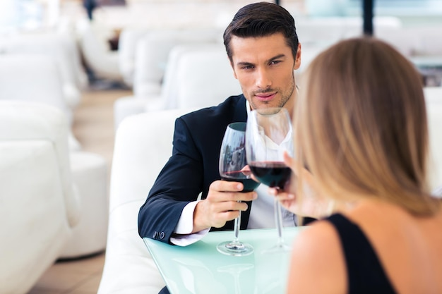 Lindo casal bebendo vinho tinto em restaurante